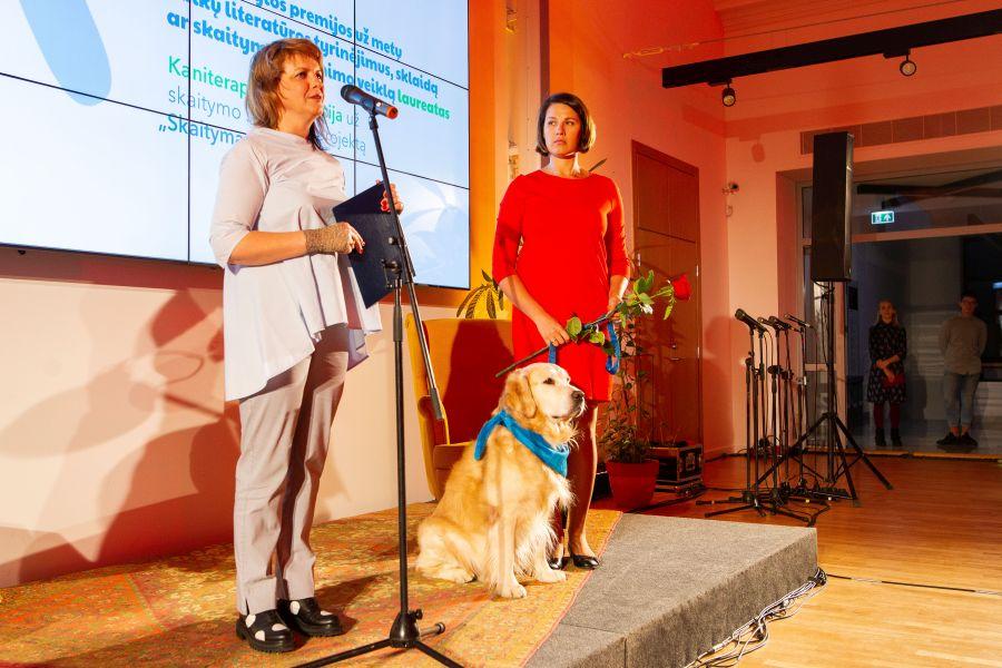 """Auksaspalvis retriveris Gongas ir projekto """"Skaitymas su šunimi"""" dalyvės Veslava Citovič-Rul bei Rasa Kardaitė-Vėlyvienė"""