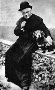 "Vaižgantas su šuneliu Kauku prie Vytauto bažnyčios. 1928 m. Nuotr. iš kn. A. Vaitiekūnienė, ""Vaižgantas"". 1982"