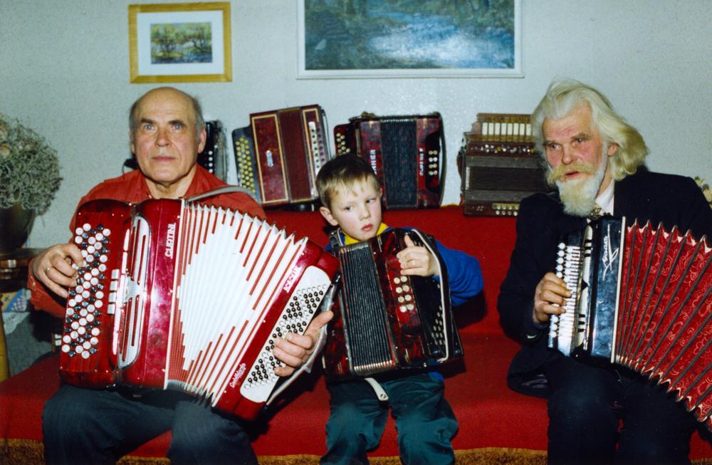 Su krikšto tėvu skulpt. Zigmantu Vaišvila (dešinėje) pas muzikos instrumentų kolekcininką.  Šiauliai, 1994 ar 1995 m.