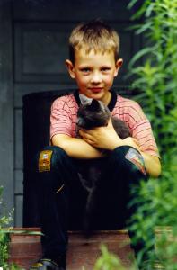 Krikšto tėvo sodyboje su mylimu katinu Pilkiu.  Šiaulių r., 1995 ar 1996 m.